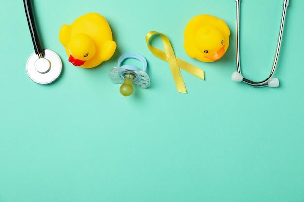 Concetto di cancro infantile con nastro di consapevolezza e accessori su sfondo di menta