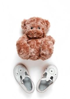 Il concetto di infanzia. sandali per bambini in pelle bianca, orsacchiotto su bianco