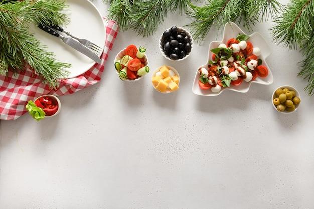 Concetto di cena di natale con insalata caprese e vari piatti di verdure per la festa di natale festiva sul tavolo bianco. vista dall'alto. spazio per il testo.