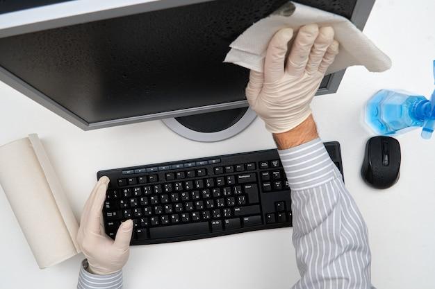 Concetto di pulizia o disinfezione dell'ufficio: un uomo d'affari pulisce il posto di lavoro, il computer, la scrivania, utilizza una pistola a spruzzo e tovaglioli di carta. pulizia delle superfici da microbi, virus e sporco.