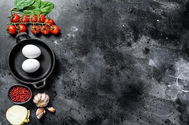 Concetto di cucina colazione con uova fritte o sode. ingredienti uova, cipolla, aglio, pomodori, peperoni, spinaci. sfondo nero.