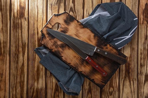 Concetto di cucina, cucina. due coltelli da cucina su un tagliere e un tovagliolo su un tavolo di legno, vista dall'alto.