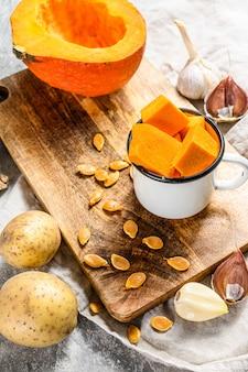 Il concetto di cucinare la zuppa di zucca. pezzi di zucca, patate, aglio, semi di zucca. zuppa di crema. sfondo grigio. cucina vegetariana