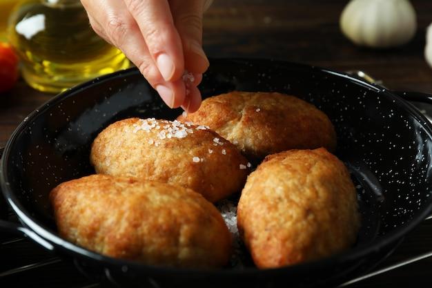 Concetto di cucinare gustose cotolette, primo piano
