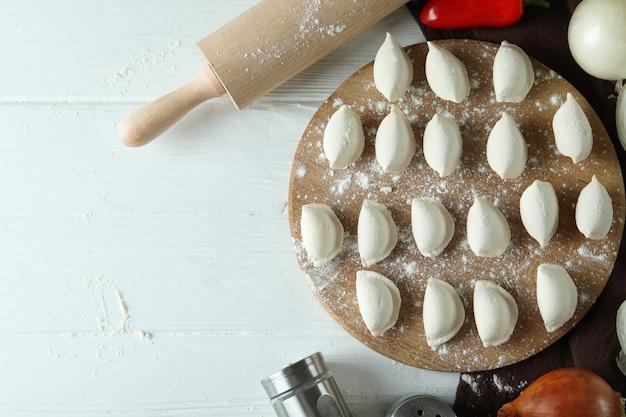 Concetto di cucinare vareniki o pierogi su un tavolo di legno bianco
