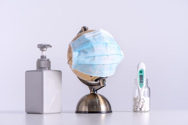 Concetto di pandemia di coronavirus covid-19 al mondo. globo con maschera facciale, disinfettante, medicina, termometro clinico isolato