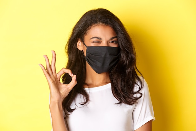 Concetto di coronavirus, pandemia e stile di vita. primo piano della ragazza afro-americana sfacciata in maschera nera, che mostra segno ok e strizza l'occhio, raccomandando qualcosa, sfondo giallo