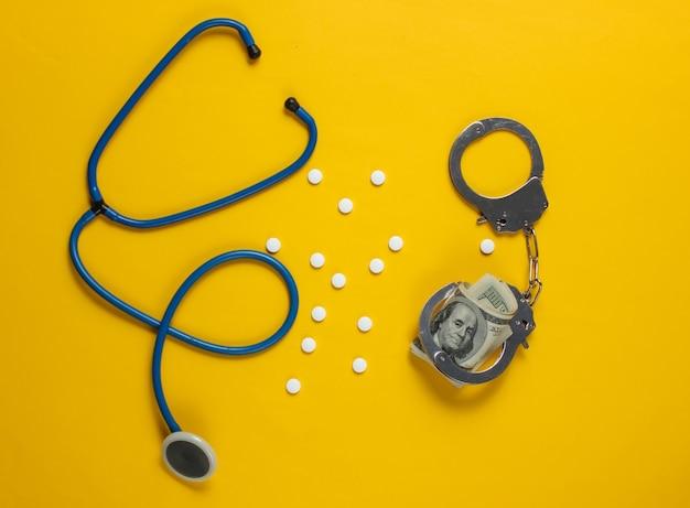 Concetto di corruzione in medicina. stetoscopio, pillole e manette con banconote da cento dollari su sfondo giallo. natura morta medica. punizione per il crimine
