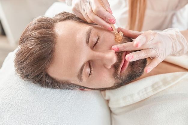 Concetto di cosmetologia e viso. un'estetista donna fa modellare il viso e la barba per un uomo che fa la ceretta. depilazione con cera.