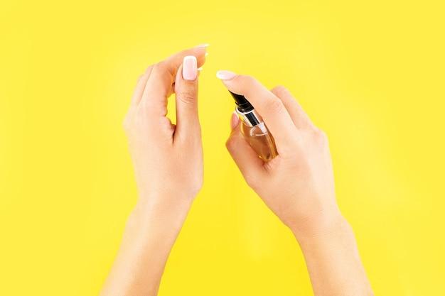 Concetto di protezione dalle epidemie covid-19 con antisettico. donna che utilizza disinfettante per le mani o gel antisettico come misura di prevenzione per il coronavirus su sfondo giallo