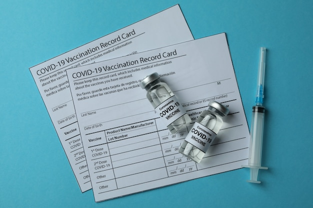 Concetto di vaccinazione covid - 19 con fiale e siringhe sul tavolo blu
