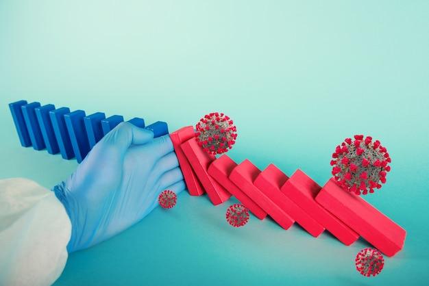 Concetto di covid19 pandemia di coronavirus con catena che cade come un gioco di domino. il contagio e la progressione dell'infezione sono stati interrotti da una mano di un medico. sfondo ciano