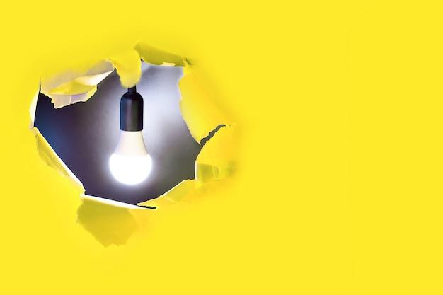 Concetto di idea creativa. una lampadina brilla in un buco di carta gialla
