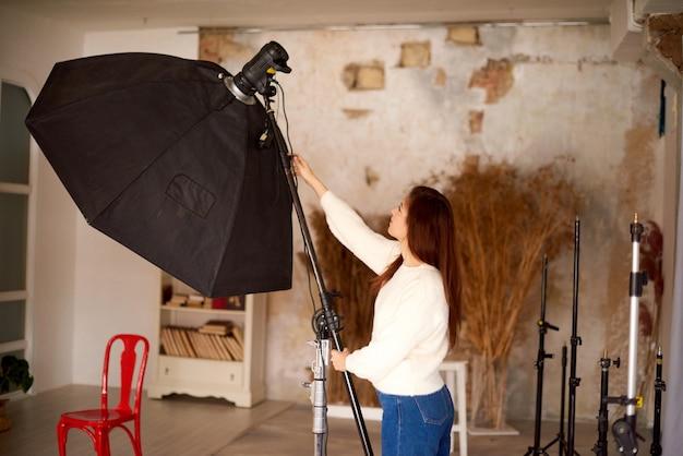 Concetto di lavoro creativo in studio fotografico donna che imposta attrezzatura fotografica