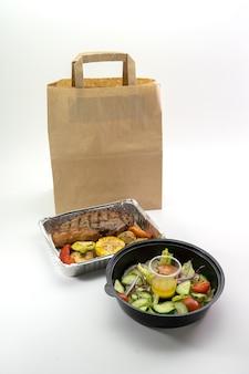 Concetto: consegna di una corretta alimentazione, bistecca e insalata di verdure