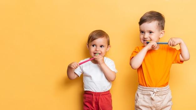 Il concetto di igiene dentale. fratello e sorella si lavano i denti insieme a uno spazzolino da denti. spazio per il testo. prevenzione della carie