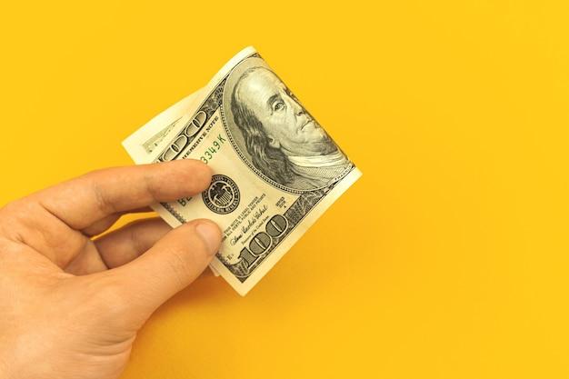 Concetto di denaro di deposito, mano con una banconota da cento dollari su sfondo giallo, foto finanziaria