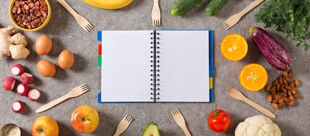 Concetto di dieta e alimentazione sana. blocco note con un programma di cibo e cibo sano