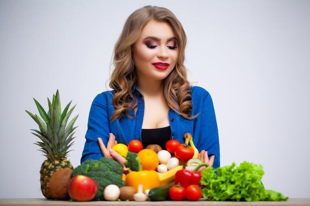 Concetto di dieta e donna in buona salute con le verdure sulla parete bianca