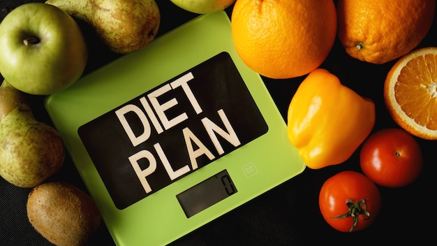 Dieta di concetto. cibo sano, bilancia da cucina. frutta e verdura scritte piano dietetico sulla superficie nera