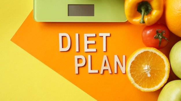 Dieta di concetto. cibo sano, bilancia da cucina. frutta e verdura scritte piano dietetico sulla superficie arancione