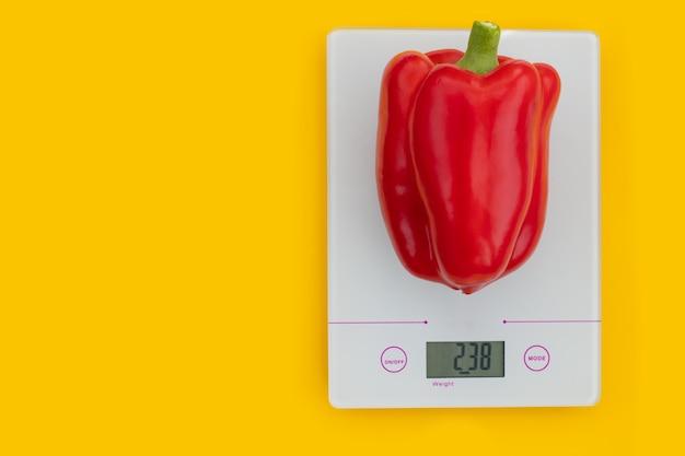 Il concetto di dieta, corretta alimentazione, alimentazione sana. peperone rosso fresco su una bilancia da cucina su sfondo giallo. prodotti di pesatura. vista dall'alto, copia spazio, layout