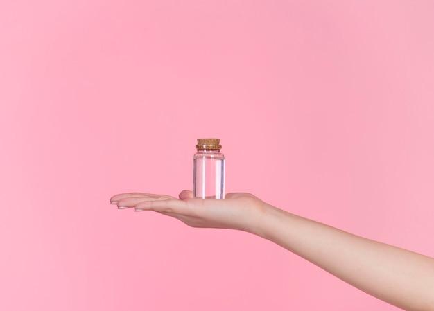 Concetto di diverse bottiglie e confezioni per prodotti cosmetici, lozioni, disinfettanti, creme. mano femminile che tiene diversi pacchetti e bottiglie.