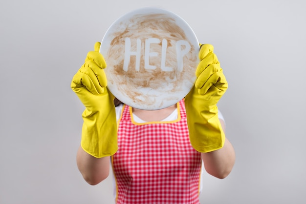 Concetto di difficoltà durante il lavaggio delle stoviglie. foto ravvicinata di sentirsi di cattivo umore moglie che soffre di duro lavoro a casa chiudendo nascondendo il viso con stoviglie bianche isolate su sfondo grigio