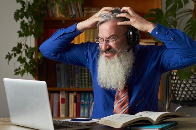 Concetto di apprendimento a distanza. insegnante frenetico dell'insegnante che esamina computer portatile e che innesta la sua testa, fuoco selettivo