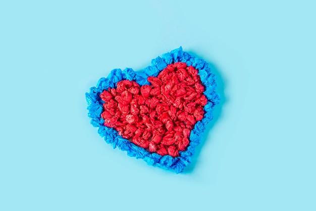 Concetto di fai da te e creatività per bambini. le mani del bambino accartocciano pezzi di carta colorata. artigianato di san valentino.