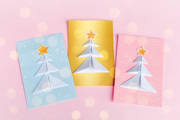 Concetto di fai da te e creatività per bambini, origami. crea biglietti di auguri blu, rosa e dorati con origami di alberi di natale