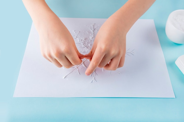 Concetto di fai da te e creatività per bambini. istruzioni passo passo: come disegnare un fiocco di neve con colla e sale. fase 4 le mani del bambino cospargono di sale sulla colla.