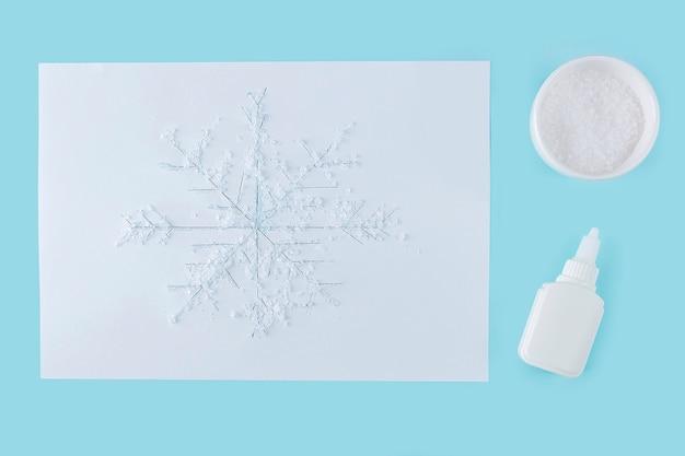 Concetto di fai da te e creatività per bambini. istruzioni passo passo: come disegnare un fiocco di neve con colla e sale. fase 4 disegno del fiocco di neve versato con colla e cosparso di sale