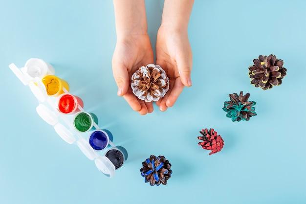 Concetto di fai da te e creatività per bambini. istruzioni passo passo: dipingere la pigna. fase 3 mani del bambino che tengono una pigna dipinta. artigianato natalizio per bambini