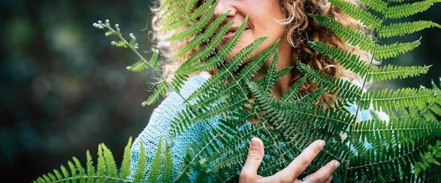 Concetto di amore e celebrazione della giornata della terra con ritratto in primo piano di una donna adulta sorridente che abbraccia una grande foglia di albero nella foresta naturale all'aperto