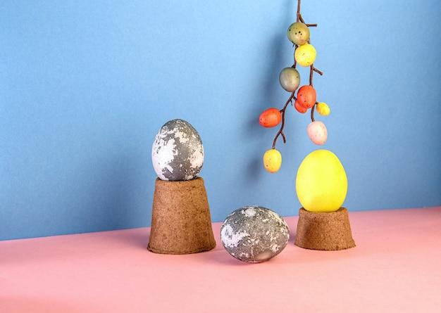 Concetto di uova di pasqua su un podio fatto di vasi di torba con uno sfondo rosa e blu pasqua astratta pasqua natura morta