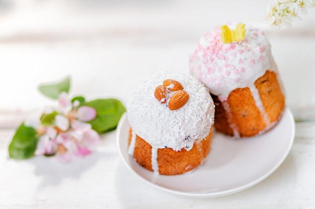 Concetto di vacanza di pasqua. vista ravvicinata di due torte pasquali decorate su un piatto con fiori di melo. vista dall'alto. copia spazio.