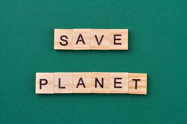 Concetto di preoccupazione per l'ecologia. testo salva pianeta scritto con cubi di legno isolati su sfondo verde.