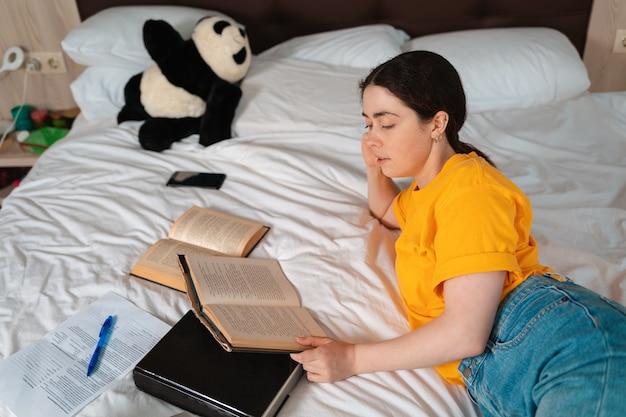 Concetto di educazione e tempo libero. bella ragazza sdraiata su un letto e leggendo un libro. vista dall'alto.