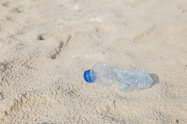 Concetto per la campagna ambientale. bottiglia plastica in spiaggia.