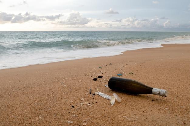 Concetto di questioni ambientali, bottiglie di bevande marroni e detriti sulla spiaggia di sabbia.