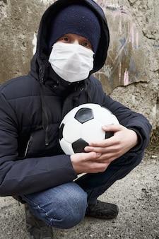 Concetto di epidemia e quarantena: un ragazzo con una maschera e una palla da solo per strada in città