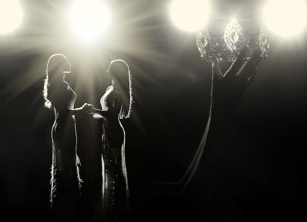 Concetto che ogni ragazza sogna di essere miss concorso di bellezza regina universo concorso. le navi da guerra delle donne sollevano diamond silver crown come vincitrice finale sul palco, illuminazione da studio con silhouette di bagliori di luce retroilluminata