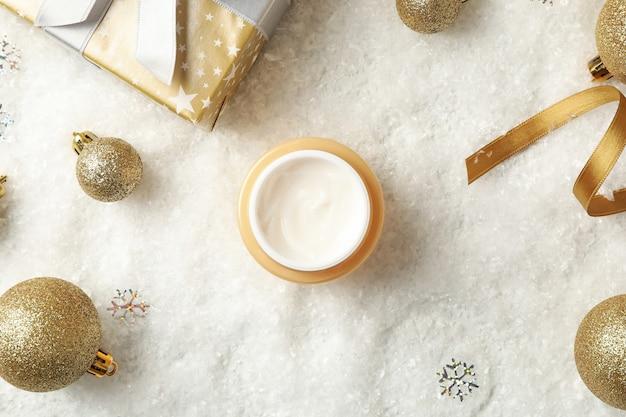 Concetto di cura del viso con cosmetici sullo sfondo con neve decorativa