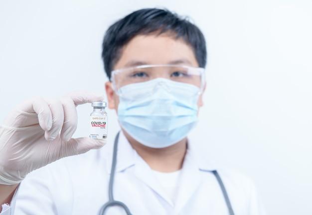 Concetto di lotta contro il virus corona virus covid-19, medico o scienziato in camicia da notte che tiene i vaccini covid-19. concetto medico e scientifico