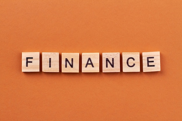 Concetto di finanza e budget. blocchetti di alfabeto con lettere isolate su priorità bassa arancione.