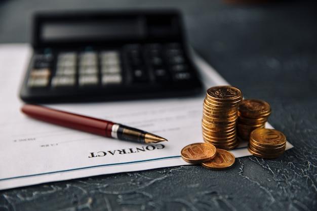 Il concetto di finanza e affari. firmare un contratto. monete e penna accanto al calcolatore