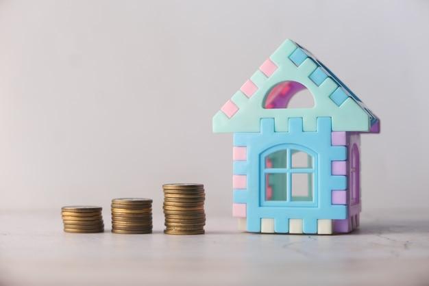 Il concetto di concetto di finanza con una pila di monete e casa sul tavolo.