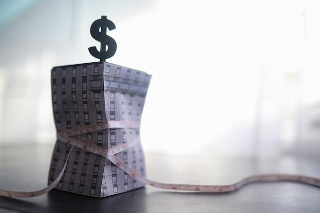 Il concetto di dipendenza finanziaria da fondi presi in prestito. debiti ipotecari. la casa sarà tirata da un metro a nastro con il simbolo del dollaro.