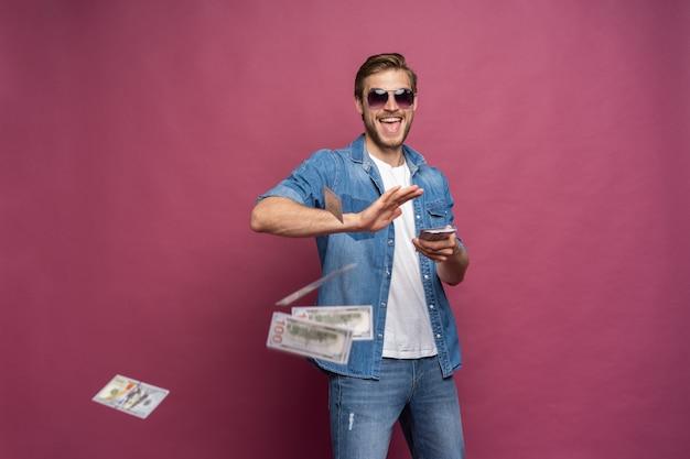 Concetto di ricchezza finanziaria, prosperità e vincite alla lotteria - uomo che butta via i suoi soldi isolati su sfondo rosa